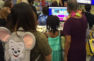 A librarian and young patron engage with new ABCmouse for Libraries activities.